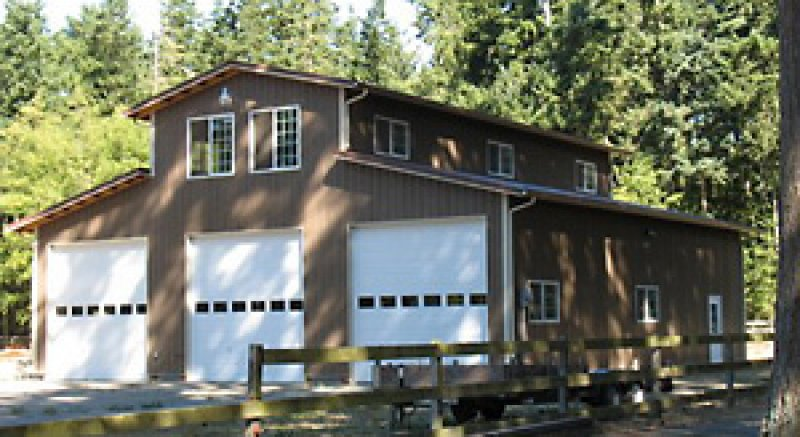 This large scale monitor type pole building features a 1,000 square-foot second floor, and has living space and lots of natural light in the upper middle bay. Note the windows in the roll-type garage doors, exterior lights, and metal siding.